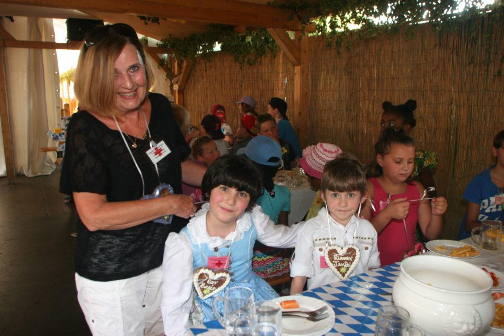 Angelika Kniesl, die ehrenamtliche Leiterin der Aktion, freut sich mit den Kindern mit.