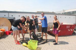 Foto (größere Gruppe vor den Garagen): MitarbeiterInnen von metafinanz beim Ausräumen der Garagen. Im Hintergrund Teamleiterin Johanna Belser und Elisabeth Pfaff (mit Sonnenhut)