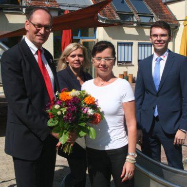 Foto: Bernhard Seidenath, Dennis Behrendt und Kathrin Ferland (hinten) begrüßen Anett Gotter mit einem Blumenstrauß.