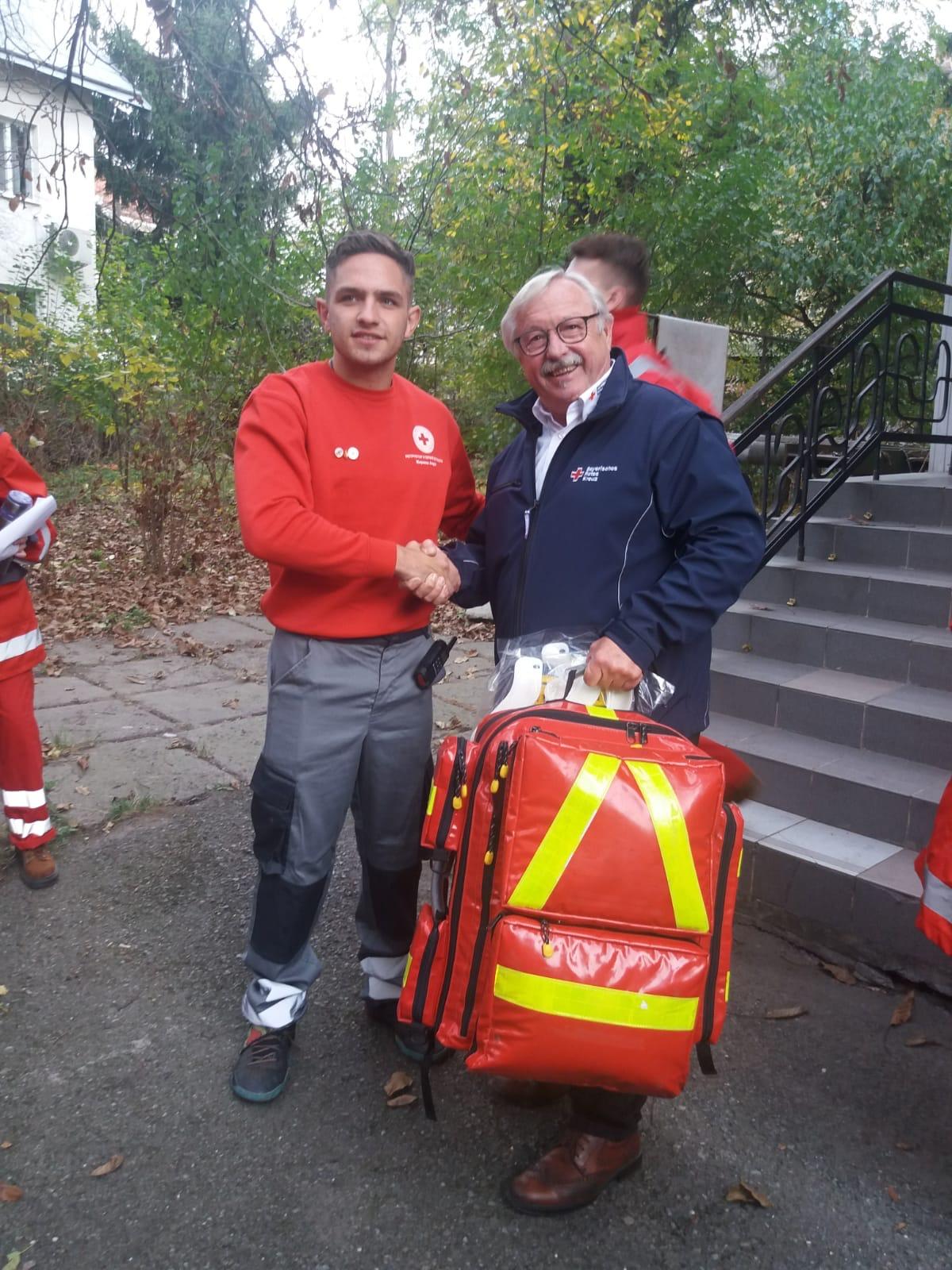 """Hans Ramsteiner (rechts) vom Dachauer Roten Kreuz übergibt den Rettungsrucksack an den Leiter der """"Schnellen Hilfe"""" Andreij"""