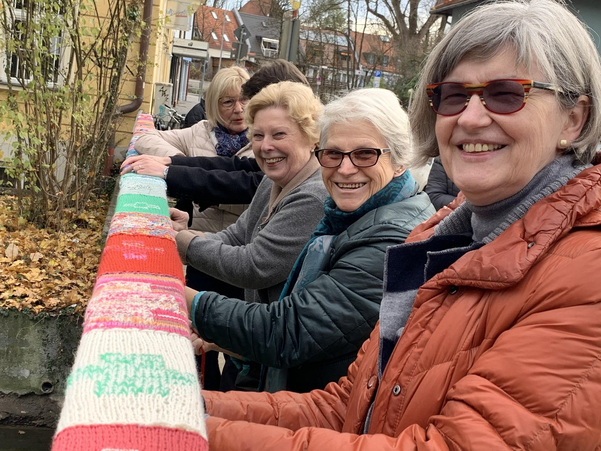 von rechts nach links: Gabriele Sölter (orange Jacke), Brigitte Göttler und Heide Schmetzer nähen die Wollrechtecke am Brückengeländer fest.