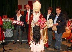 Der Nikolaus überreicht einem Kind sein Geschenk. Im Hintergrund (von li nach re) Angelika Kniesl, Bernhard Seidenath, Angelika Gumowski und Renate Hirtreiter