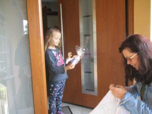Tatü-Tata-Leiterin Anett Gotter bringt einem Kind ein Geschenk an die Haustür.