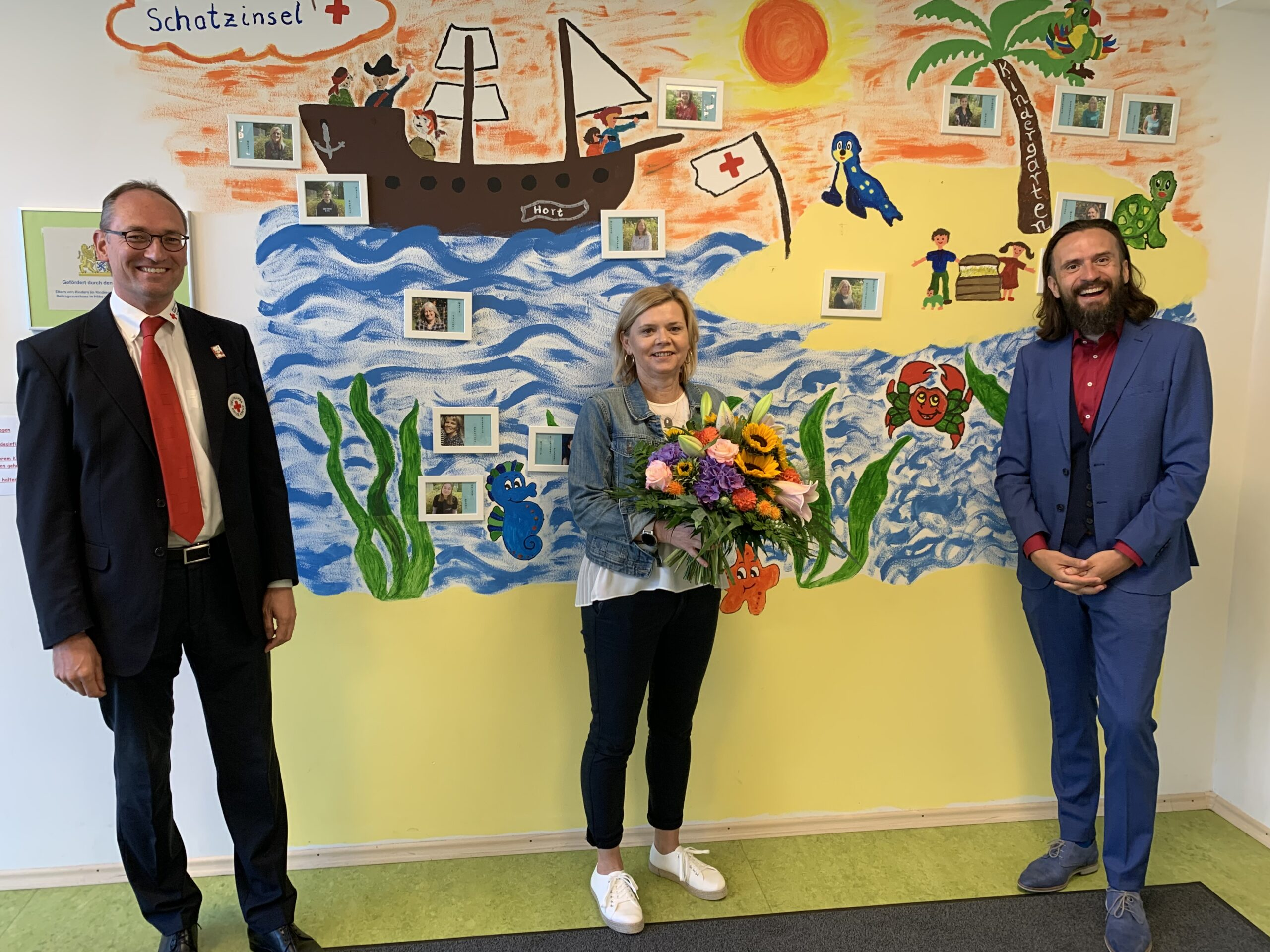 Foto: Mit einem Blumenstrauß wurde Kathrin Ferland vom BRK-Kreisvorsitzenden Bernhard Seidenath und vom BRK-Kreisgeschäftsführer Paul Polyfka in der Schatzinsel in Karlsfeld begrüßt.