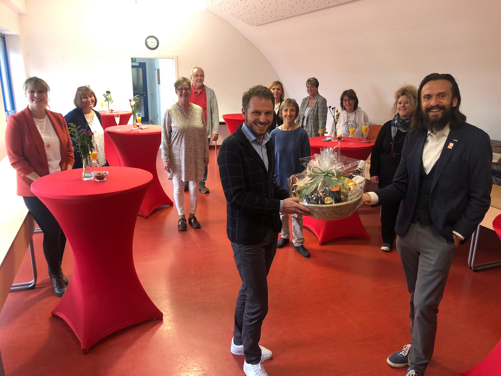 Paul Polyfka (rechts) und Leiter*innen der Kinderhäuser begrüßen Markus Fuchs mit einem Geschenkkorb.