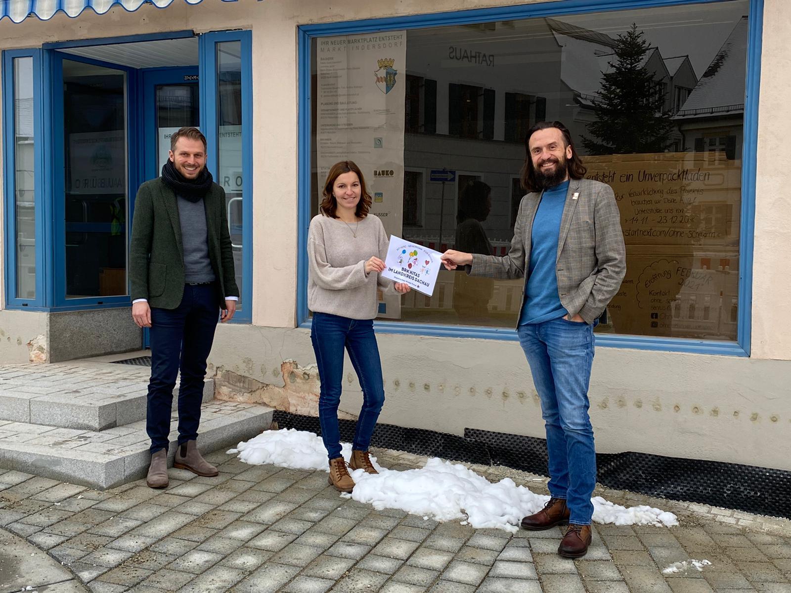Paul Polyfka (rechts) übergibt Jessica Schilcher das BRK-Kita-Logo für die Sponsorenwand. Links: Markus Fuchs.